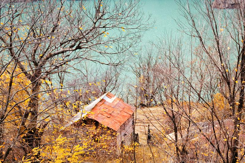 Old house near lake, surrounded by autumn trees, hunting lodge in forest royalty free stock photos