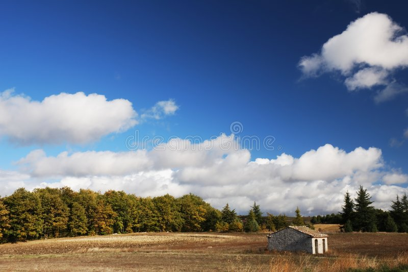 Old house in picturesque field. Scenic view of old stone house in picturesque field or meadow with trees, blue sky and cloudscape background stock photo