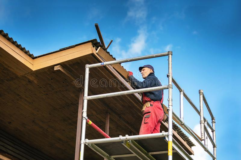 Old house renovation - construction worker installing new planks on house roof eaves royalty free stock photography