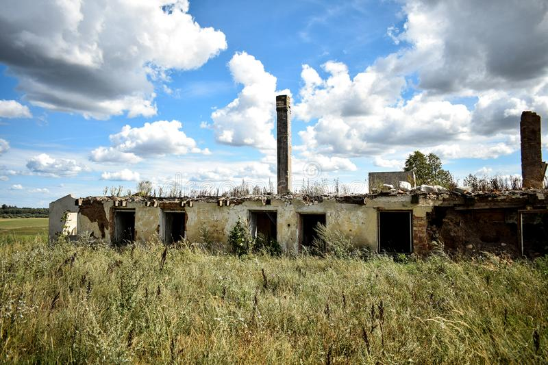 Old house ruins in the country side of Latvia. Old House ruins in the country e of Latvia, Beautiful sky with white fluffy clouds and house with chimney on top stock photos