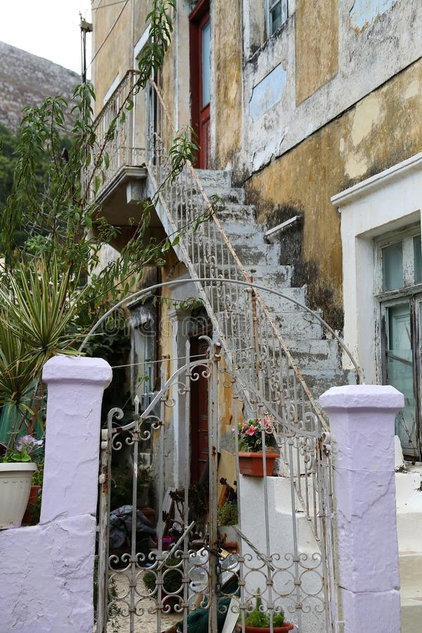 An old house and it`s old style iron ladder in a center city streets behind the coastal in Calymnos Island. Dodekanes royalty free stock images