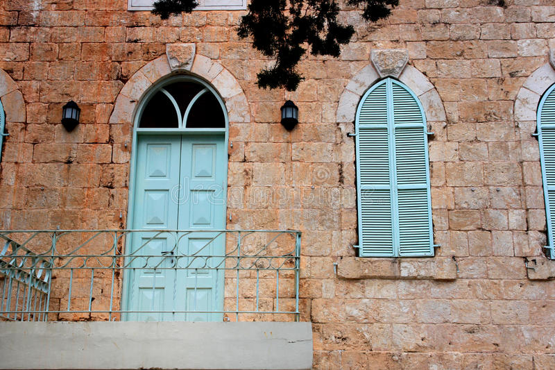 Old house's wall from jerusalem stone with old blue balcony. filtered image stock photo