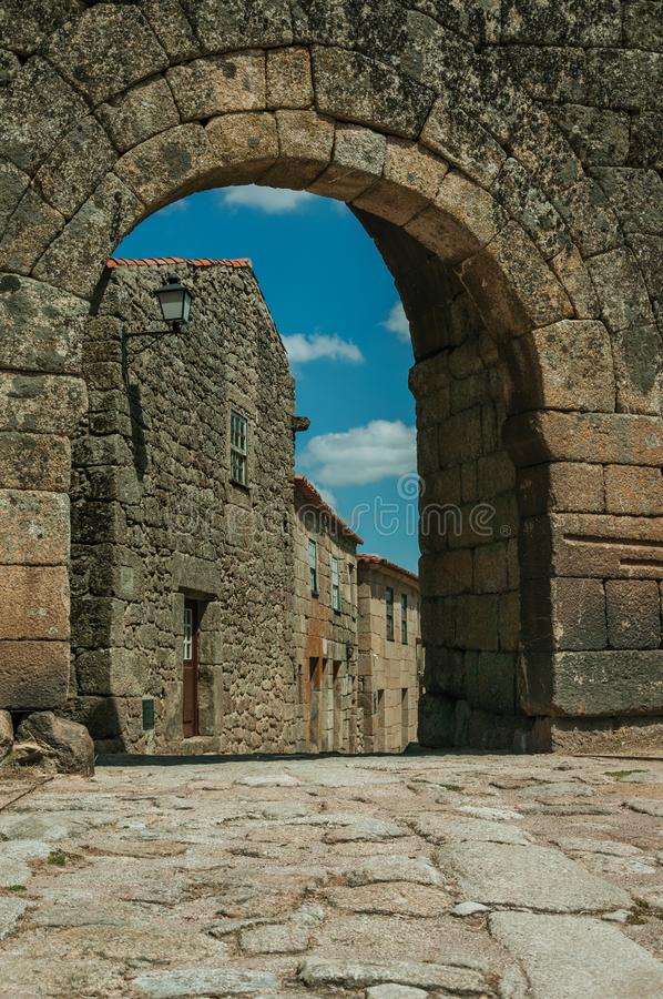 Old house seen through arch gate from a stone wall. Old house with wooden door on deserted alley seen through arch gate from a stone wall, in a sunny day at royalty free stock photos