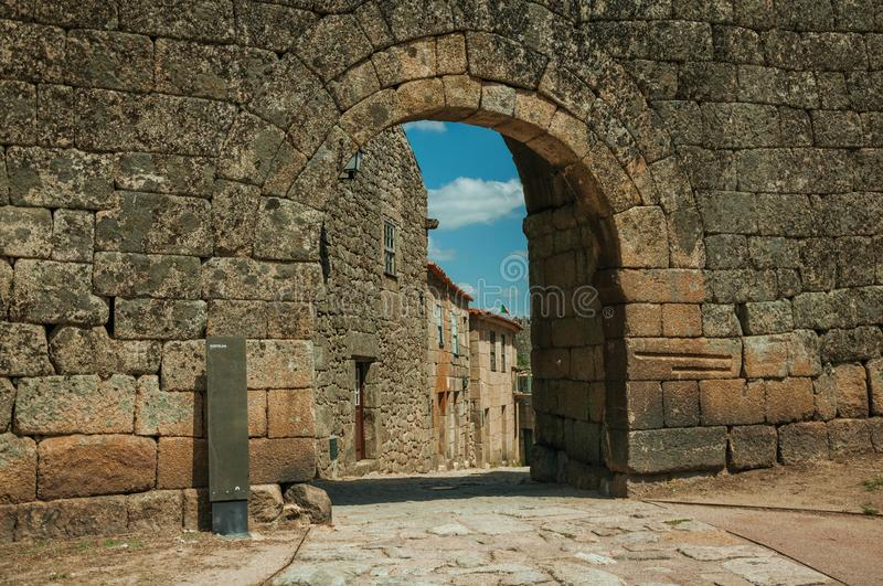 Old house seen through arch gate from a stone wall. Old house with wooden door on deserted alley seen through arch gate from a stone wall, in a sunny day at royalty free stock image