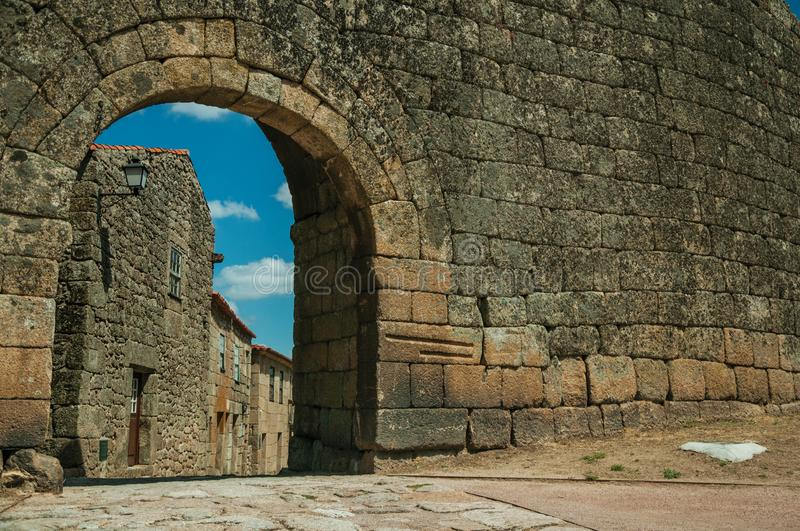Old house seen through arch gate from a stone wall. Old house with wooden door on deserted alley seen through arch gate from a stone wall, in a sunny day at royalty free stock photography