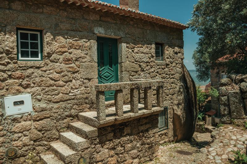 Old house with stone staircase in Monsanto. Charming facade of old house with stone staircase going to a small porch on deserted alley, in a sunny day at royalty free stock photo