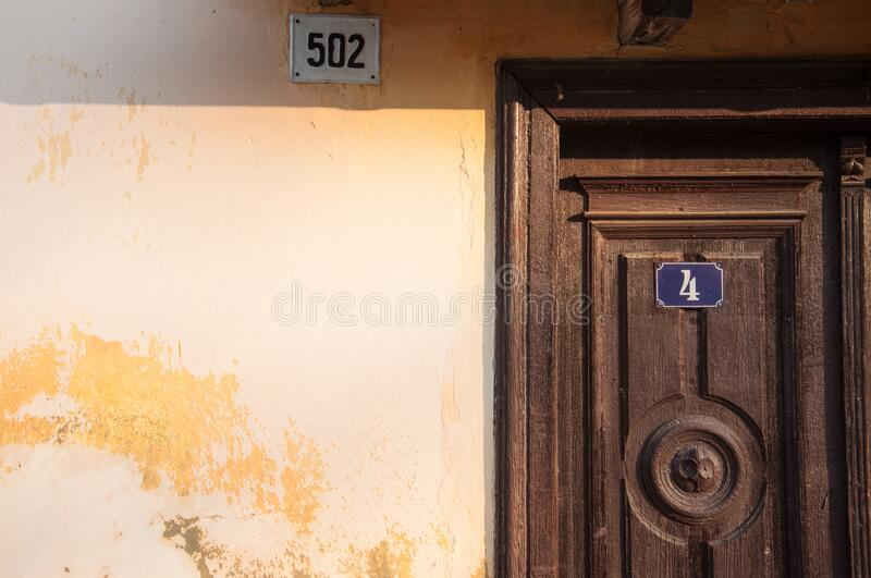 Old house. Wall and woden door with a house number stock photography