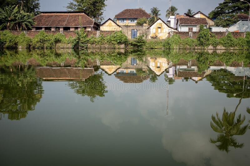 Old houses reflecting on a pond, Kochi, Kerala, India. Old houses reflecting on a pond, with no people, in the historical district of Kochi, Kerala, India stock photography