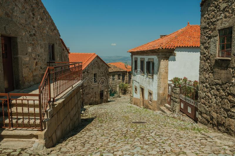 Old houses and stone staircase on cobblestone alley. Facade of old houses and stone staircase with iron railing on cobblestone alley at Linhares da Beira. A stock photo