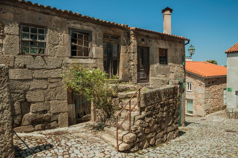 Old houses and stone staircase on cobblestone alley. Facade of old houses and stone staircase with iron railing on cobblestone alley at Linhares da Beira. A royalty free stock images