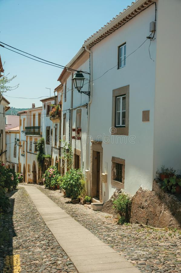Old houses with whitewashed wall in an alley on slope stock images