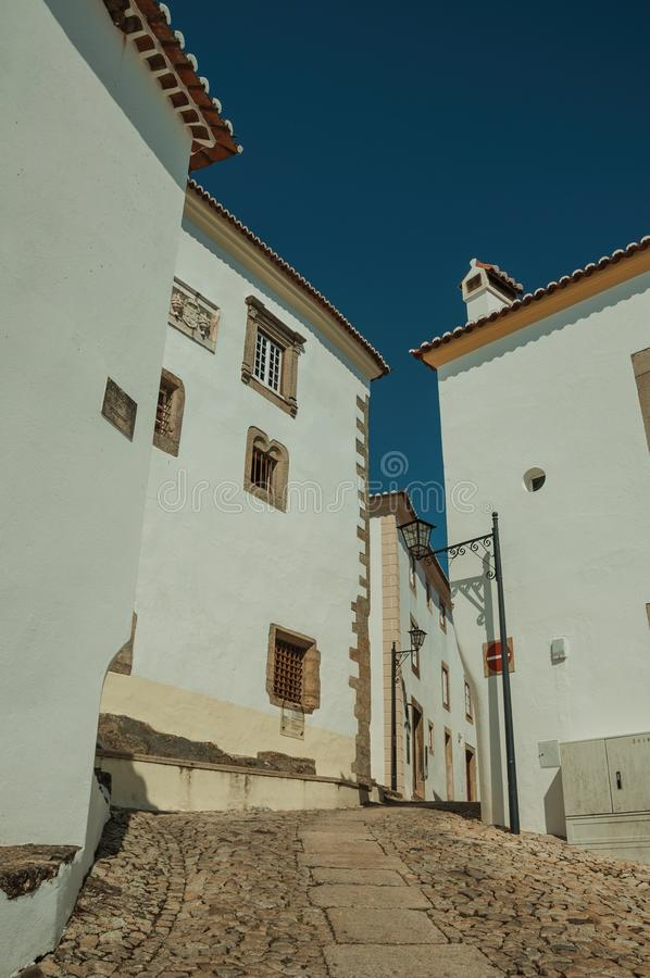 Old houses with whitewashed wall in cobblestone alley on slope royalty free stock images