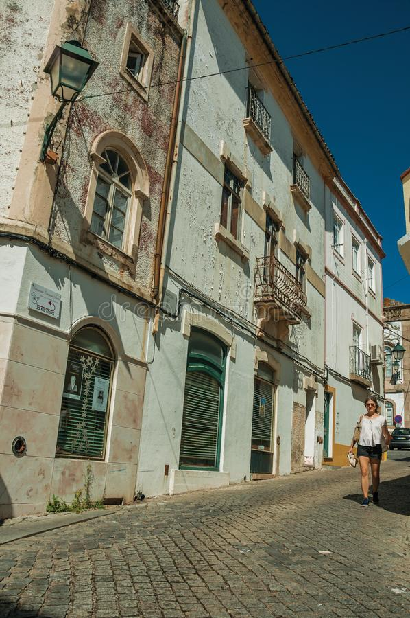 Old houses and woman walking down the street stock photo