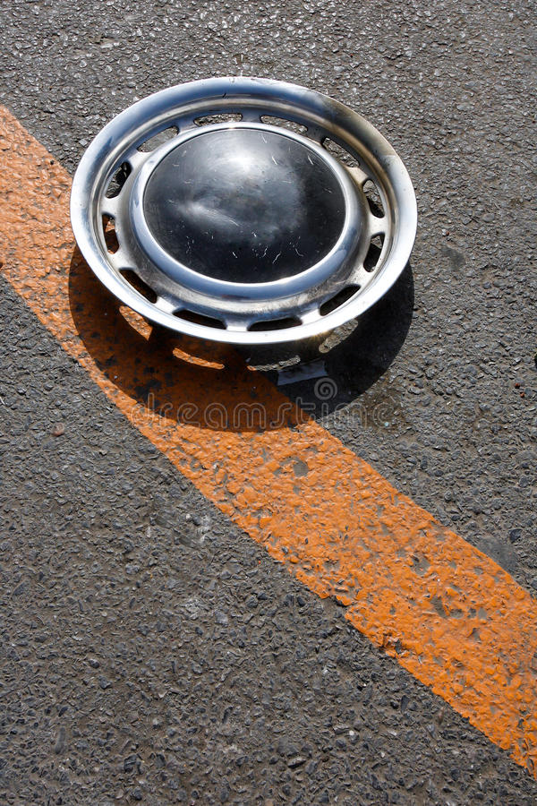 Old hubcap. An old hubcap at the street stock photo