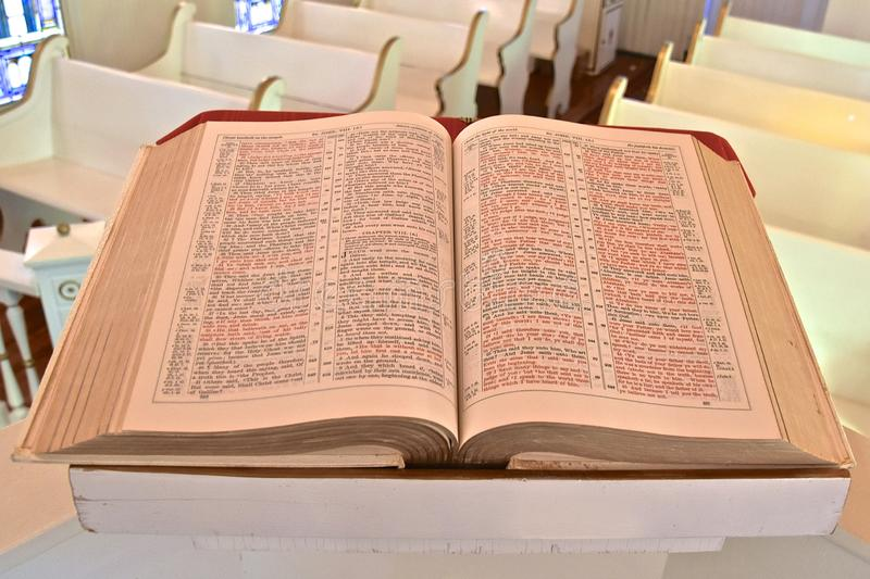 Old huge Bible opened to the Book of John. A huge old bible opened to the Book of John rests on a pulpit in a small chapel stock photo