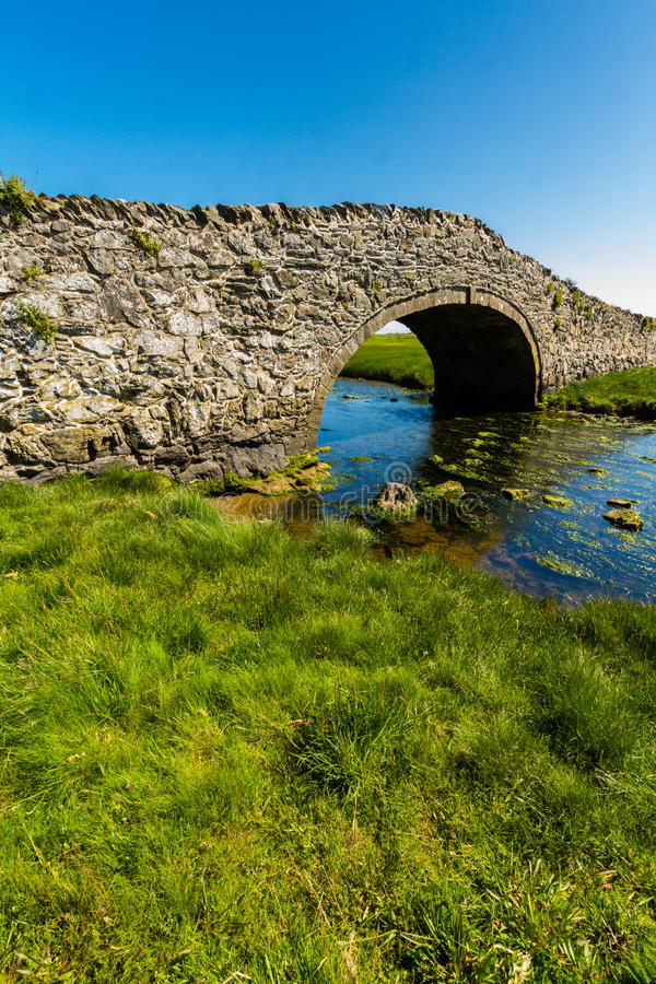Old Hump Back Bridge, Aberffraw, Anglesey. Eighteenth Century stone hump back bridge, with water channel, the river Ffraw, and blue sky. Aberffraw, Anglesey stock photo
