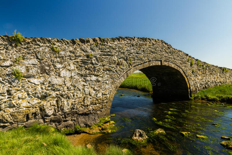 Old Hump Back Bridge, Aberffraw, Anglesey. Eighteenth Century stone hump back bridge, with water channel, the river Ffraw, and blue sky. Aberffraw, Anglesey royalty free stock image