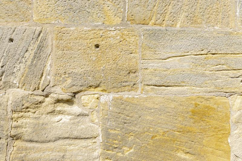 Old idyllic, beautifully restored sandstone wall of a historic building of yellow sandstone with various surface structure, some. Stones have leaching and holes stock photos