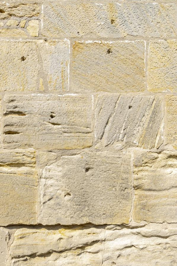 Old idyllic, beautifully restored sandstone wall of a historic building of yellow sandstone with various surface structure, some. Stones have leaching and holes stock photo