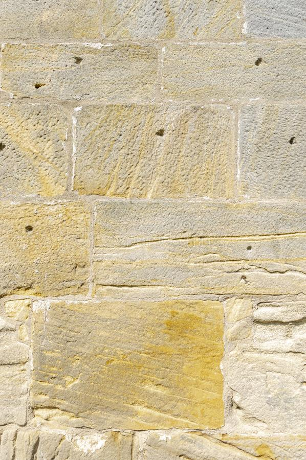 Old idyllic, beautifully restored sandstone wall of a historic building of yellow sandstone with various surface structure, some. Stones have leaching and holes royalty free stock photography