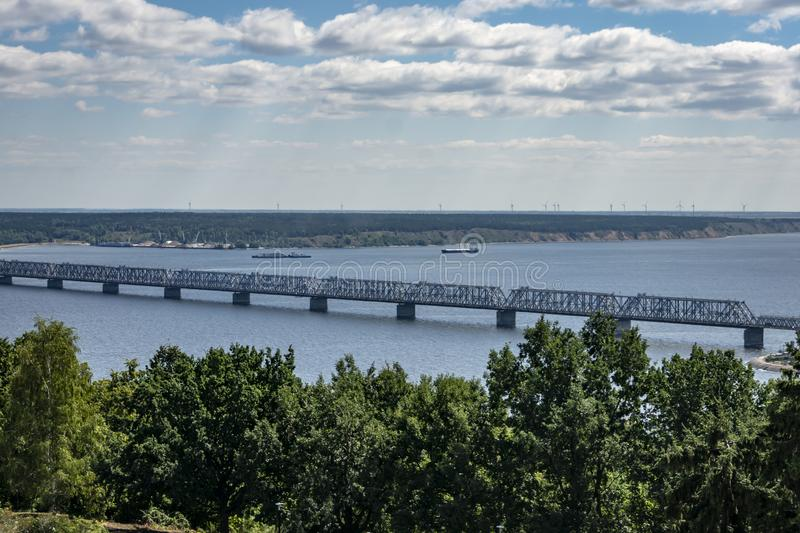 Old Imperial Bridge over the Volga River in Ulyanovsk. Bridge was built in 1916. Green banks and blue smooth surface of the rive stock images