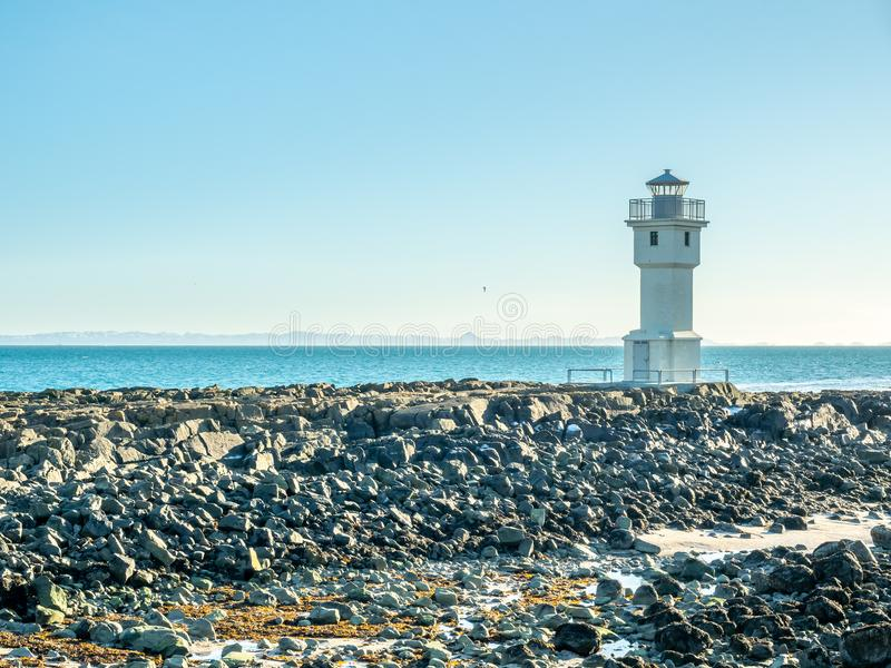 Old inactive Arkranes lighthouse, Iceland. The old inactive Arkranes lighthouse at end of peninsula, was built since 1918, under blue sky, Iceland royalty free stock images