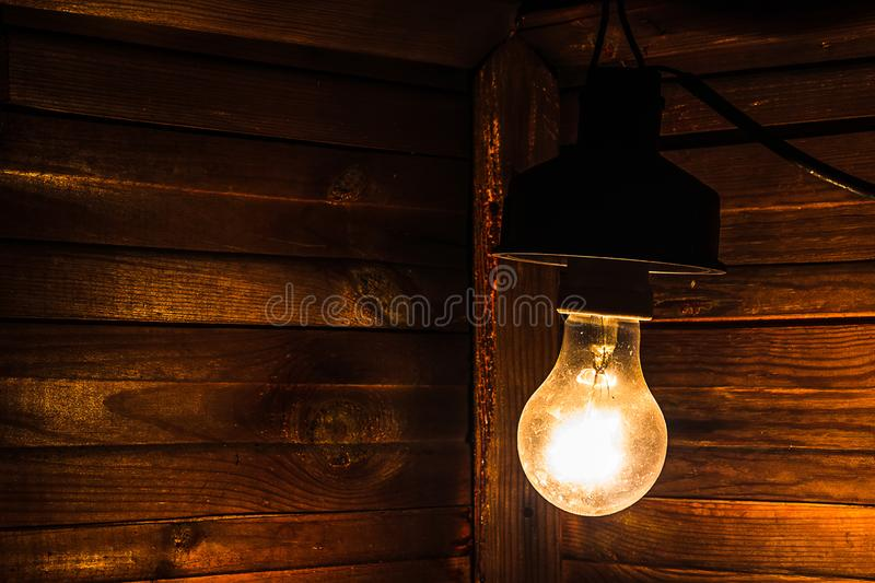 An old incandescent lamp illuminates the corner of a dark room. Electrification, payment for electricity.  stock photo