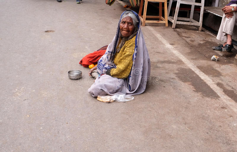 Old Indian beggar waits for alms on a street in Pushkar, India stock photo