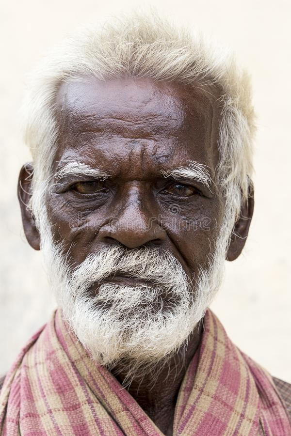 Old indian poor man with a dark brown wrinkled face and white hair and a white beard, serious or sad royalty free stock photos