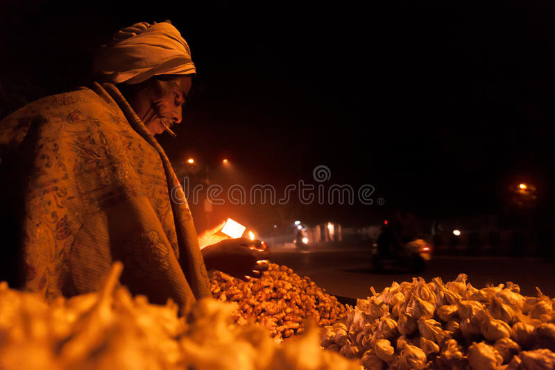 Old indian street vendor smoking in winter royalty free stock photo
