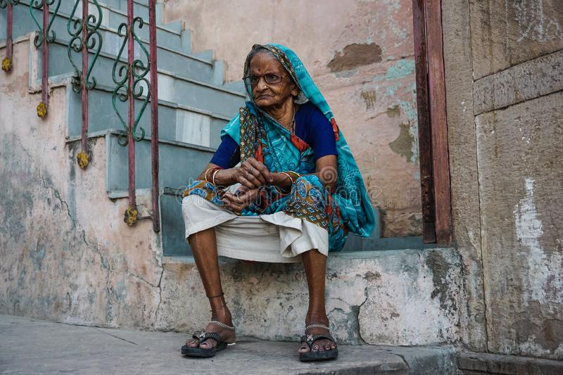 Varanasi, INDIA - MAY 29, 2017: Old Indian woman sitting on the stairs royalty free stock photos