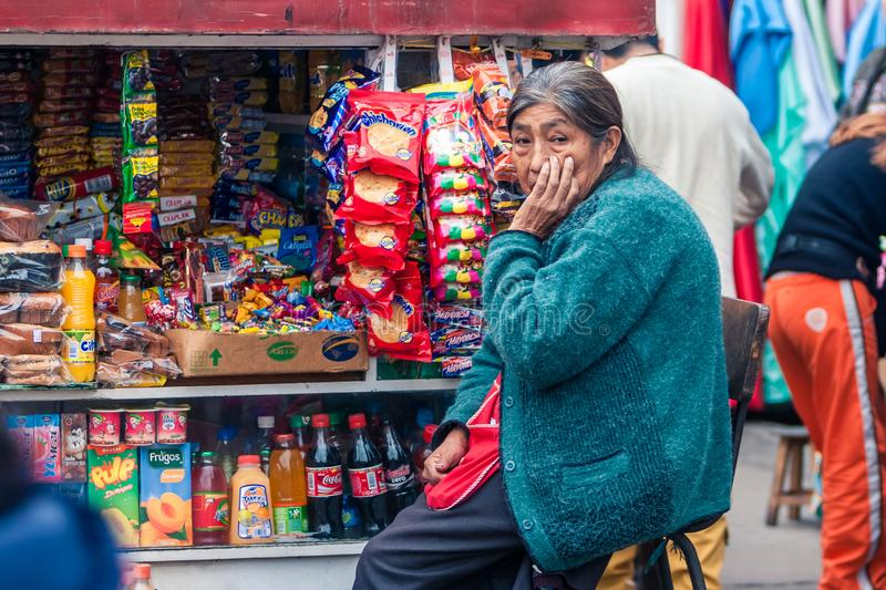 Lima / Peru Jun 13.2008: Old indigenous woman seating next to the colorful Newsstand stock image