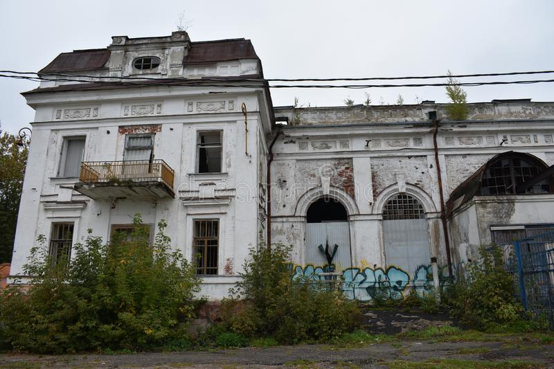 Old industrial building of the Russian Empire, young trees sprouted. On the roof stock photo