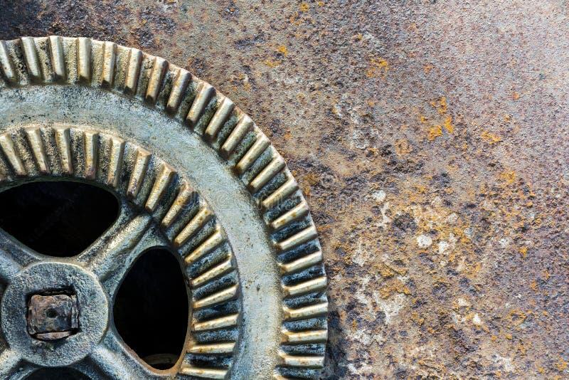 Old industrial gear wheel against rusty metal background. Big old industrial gear wheel against rusty metal background royalty free stock images