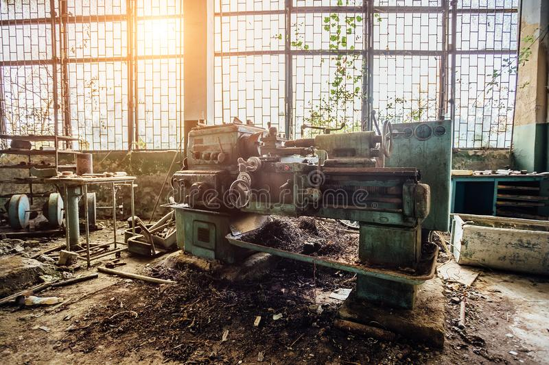 Old industrial machine tool. Rusty metal equipment in abandoned overgrown factory.  royalty free stock images