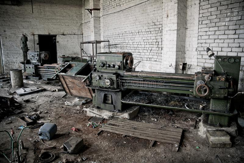 Old industrial machine tools and rusty metal equipment in abandoned factory.  royalty free stock photography