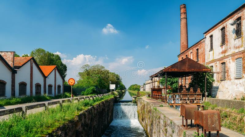 Old industrial warehouses alongside a cascade on a lock at the Naviglio Pavese, a canal that connects the city of Milan with Pavia stock photography