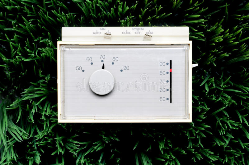 An old inefficient thermostat. On grass stock photos