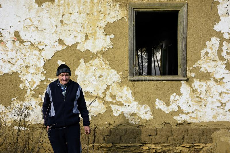 Old inhabitant in front of an old house of Jurilovca royalty free stock images