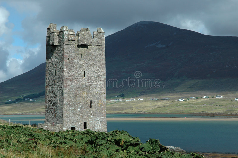 Old Irish castle tower. An old castle tower ruin on Achill Island (Ireland) on a sunny day. In the background a large hill on the mainland with an Irish village royalty free stock image