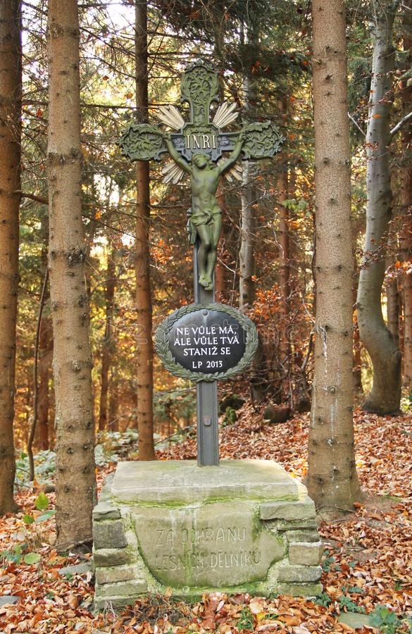 Old iron cross. With Jesus and written prayer in the forest, Beskydy mountains, Czech Republic royalty free stock image