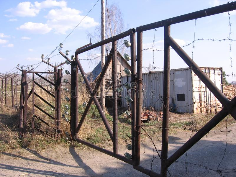 An old iron fence with a closed rusty gate prohibits travel to the territory of an abandoned technical station royalty free stock image