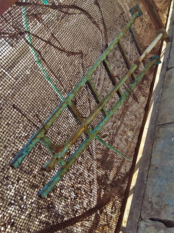 Old iron staircase hanging on the fence mesh stock photo
