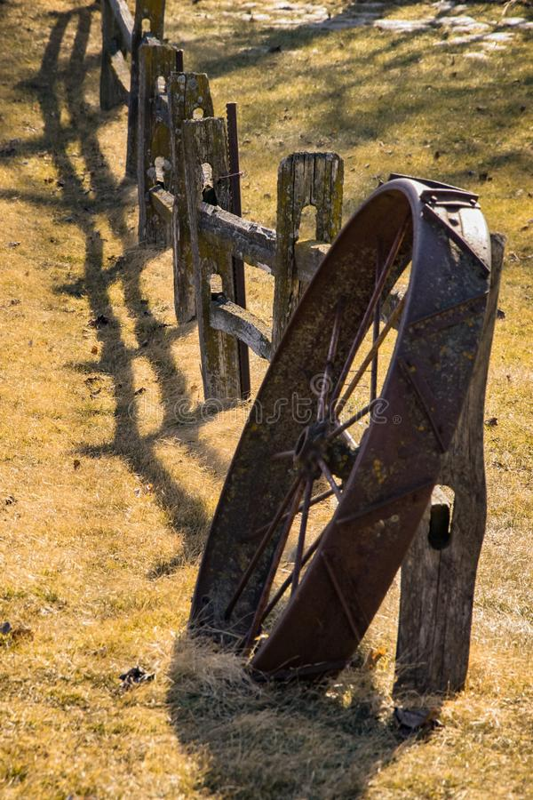 Old iron wagon wheel and wooden fence royalty free stock images