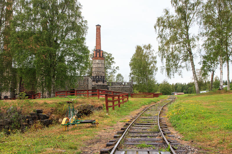 An old Ironworks Kiln in Galtstrom Sweden. With the supply train tracks in the foreground and an old train track bicycle on the side royalty free stock photos
