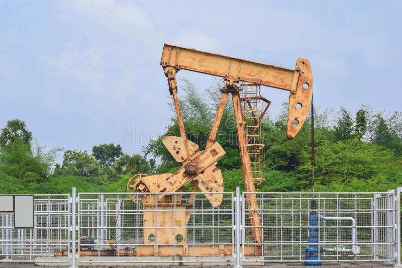Old isolated rusty oil pump jack extracting crude oil and natural gas form well in green and cloudy oil fields of India, Asia. 