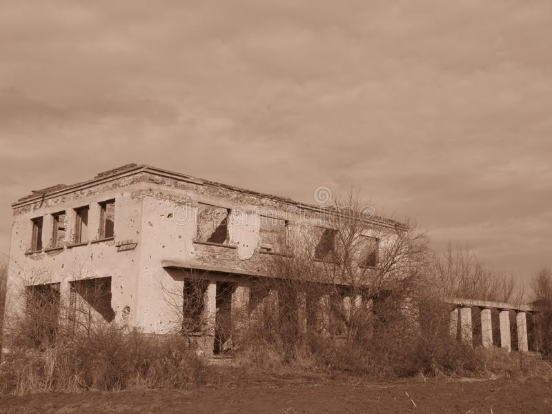 Old isoleted demolished abandoned building overgrown with bushes and shrubs in Sepia colour. Building houses remains. Building without roof. Obsolete housing stock photography