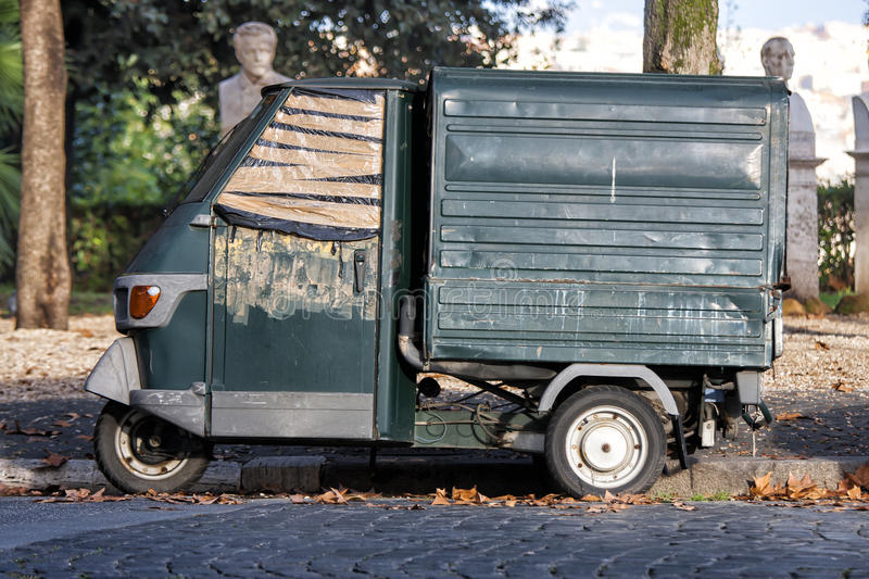 Old Italian car parked in a historic park (Rome, Italy). The small car has a broken window. Tape covering the hole. The Piaggio Ape (Italian for bee), sometimes stock photography