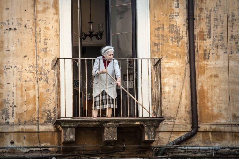 Old italian lady sweeping balcony. Catania, Sicily. Italy royalty free stock image