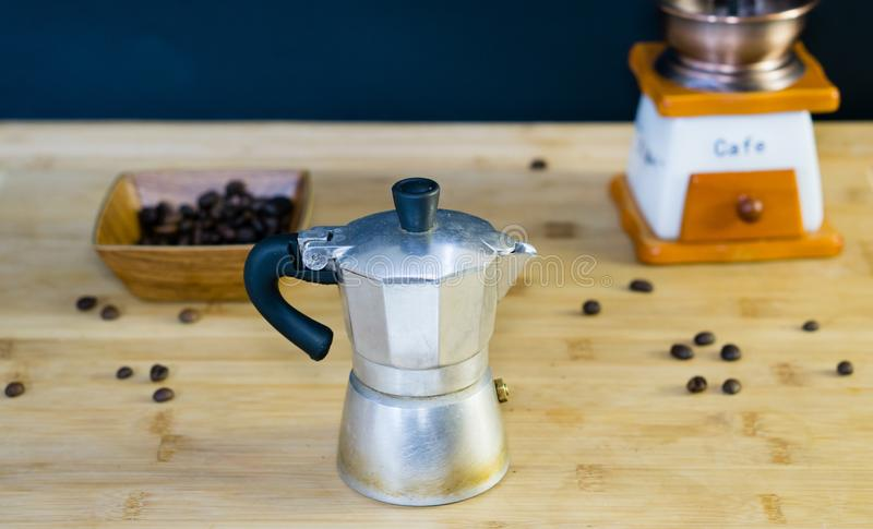 Old Italian Moka coffee maker, manual coffee grinder in the background. And roasted coffee beans in a wooden dish, wooden background stock images